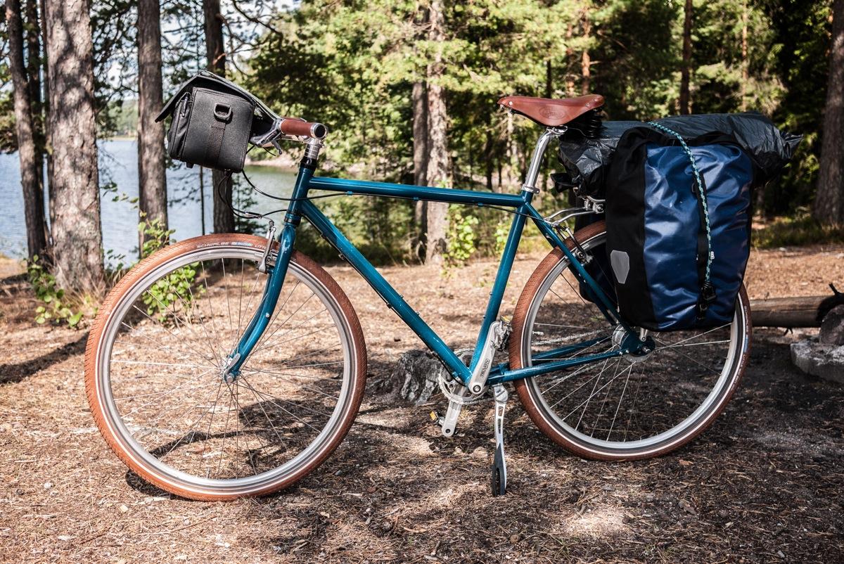 Stahlrahmen fahrrad in Ozeanblau mit braunen schwalbe Reifen und Brooks sattel flyer. Ausgestattet mit gepäcktaschen von ortlieb. Das Bild ist bei einer fahrradtour in schweden entstanden.