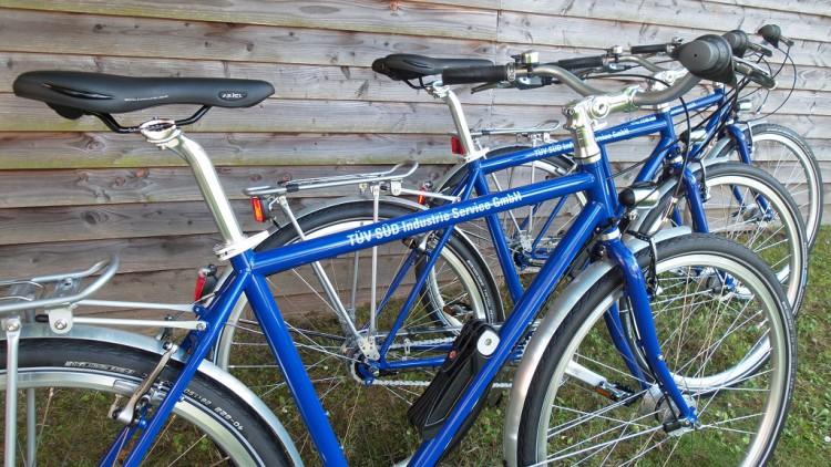 """Firmenfahrräder vom TÜV Süd in blau. Die Fahrräder sind beschriftet mit dem Logo vom """"TÜV Süd"""". Ausgestattet für den Einsatz im Gelände."""