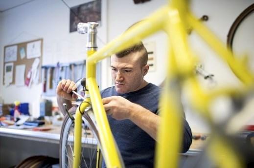 Gelbes Fahrrad in der Monatge mit Fahrradmechaniker