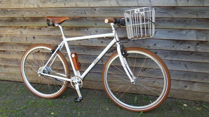Weißes Herrenrad mit braunem Sattel und braunen Reifenvor Holzwand