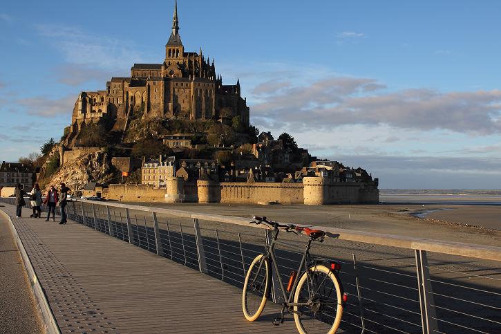 Trekkingrad der Fahrradmanufaktur Kreativrad. Stahlrahmen Fahrrad mit Schwalbe Fat Frank Reifen in creme. Ausgestattet mit einer NuVinci N380 und edlen Brooks Flyer Sattel. Die Farbe des Trekkingrades ist Schiefergrau. Das Fahrrad steht vor der Abei des Mont Saint-Michel.