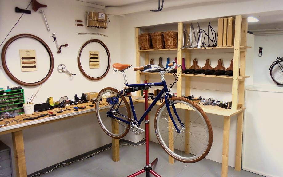 """blaues Herren Fahrrad das in der Werkstatt hängt das Fahrrad ziert die aufschrift """"Paulaner"""""""