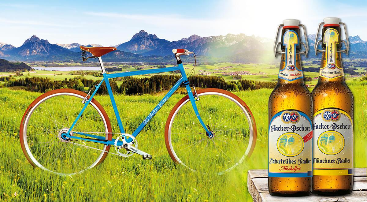 Retrobike blau auf einer Wiese mit Bergen im Hintergrund und zwei Hacker Pschorr Bierflaschen
