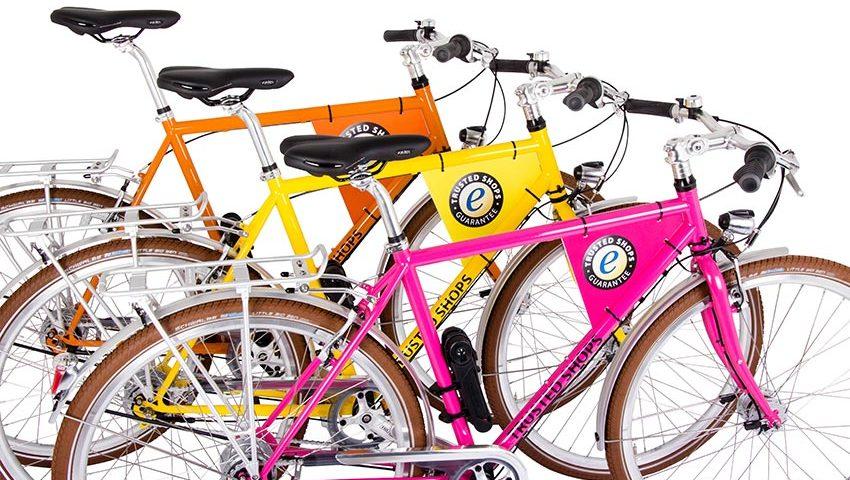 ein gelbes, ein oranges und ein pinkes herrenfahrrad mit der aufschrift trusted shop