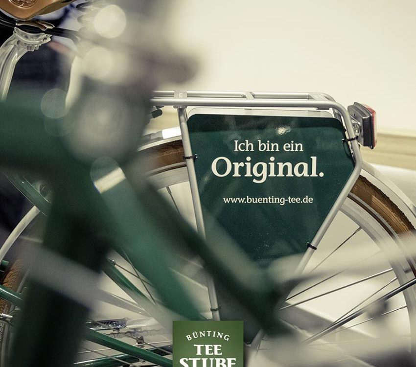 """Fahrrad Werbeschild am Gepäckträger in grün. Beschriftet mit """"Ich bin ein Original"""" der Firma Büntingtee."""