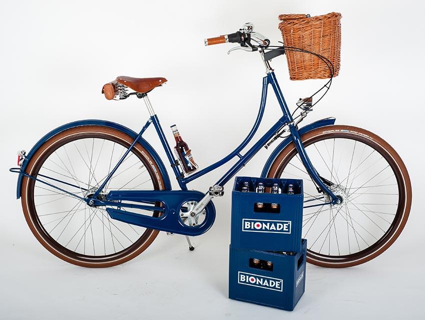 blaues Hollandrad mit holzkorb, Ledersattel und Getränkehalter. Im hintergrund zwei Bionade kisten