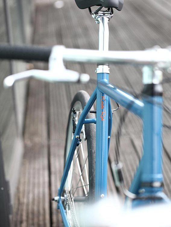 Blaues Singlespeed Bike, mit einem schwarzen Selle Royal Sattel Match, Schwalbe Kojak Bereifung und Deore V-Brakes..