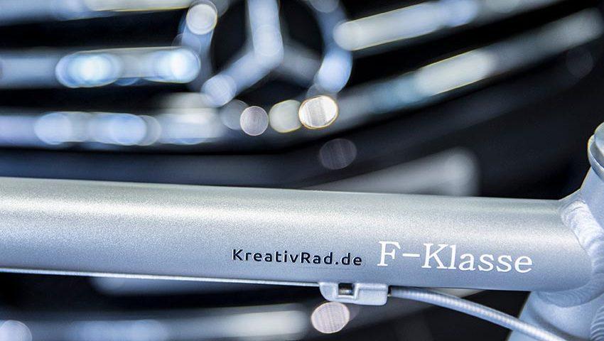 """Fahrradrahmen in silber. Im Hintergrund steht ein Mercedes. Auf dem Rahmen ist """"F-Klasse"""" eingebrannt."""