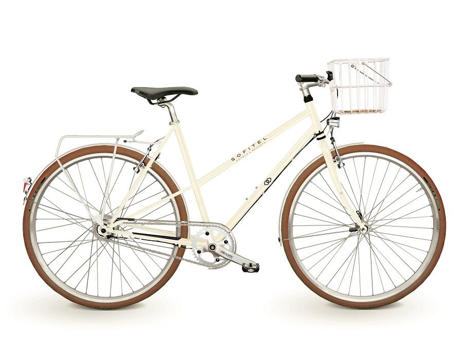 Fahrrad in weiß mit der Aufschrift Sofitel Hotel mit Brooks Hoxton Korb und braunen Reifen. Es ist ein Leihfahrrad der Hotelkette Sofitel.