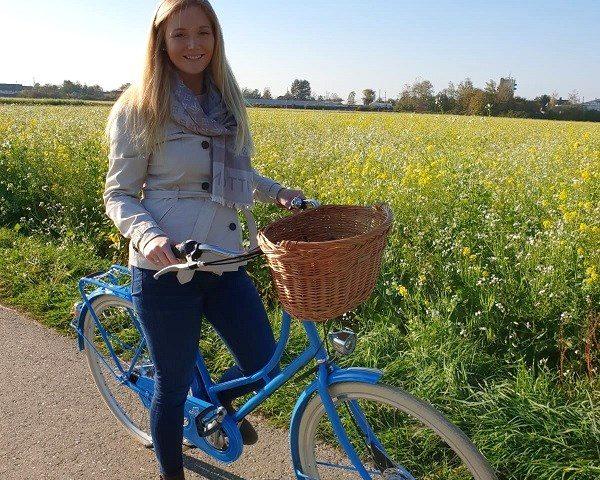 Hollandrad in hellblau, blonde frau, gefolchtener weiden fahrradkorb in hellbraun, helle creme schwalbe reifen road cruiser, rapsfeld im hintergrund