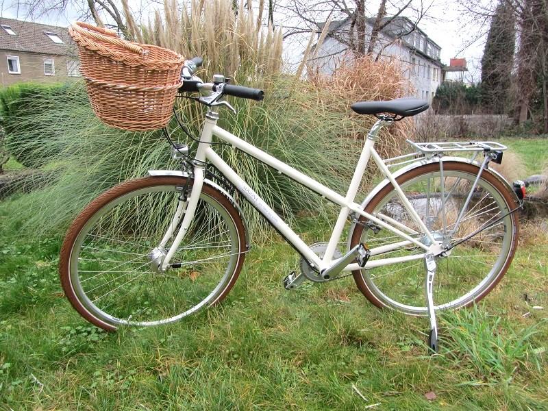Citybike in der farbe elfenbein, mit Fahrradkorb aus Flechtrohr von basil, braune schwalbe road cruiser reifen, sattel von selle royal ariel, shimano 8-gang nexus Nabenschaltung, hinterbauständer comp zoom von pletscher