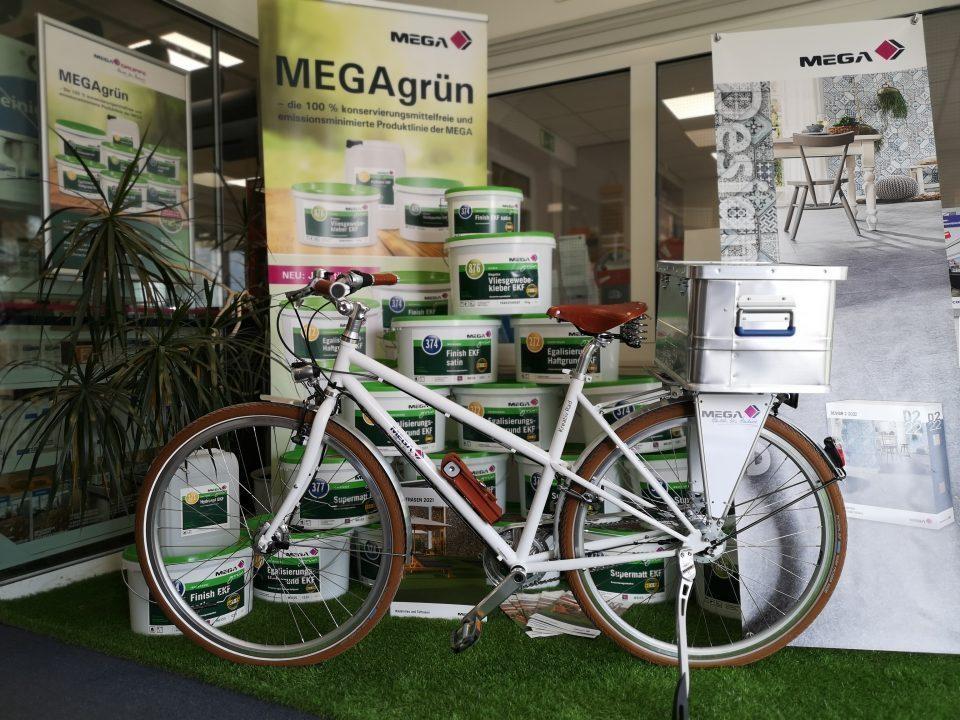 Dienstfahrrad in weiß mit Firmenlogo. Mit Fahrradkiste aus Aluminium auf dem Gepäckträger befestigt.
