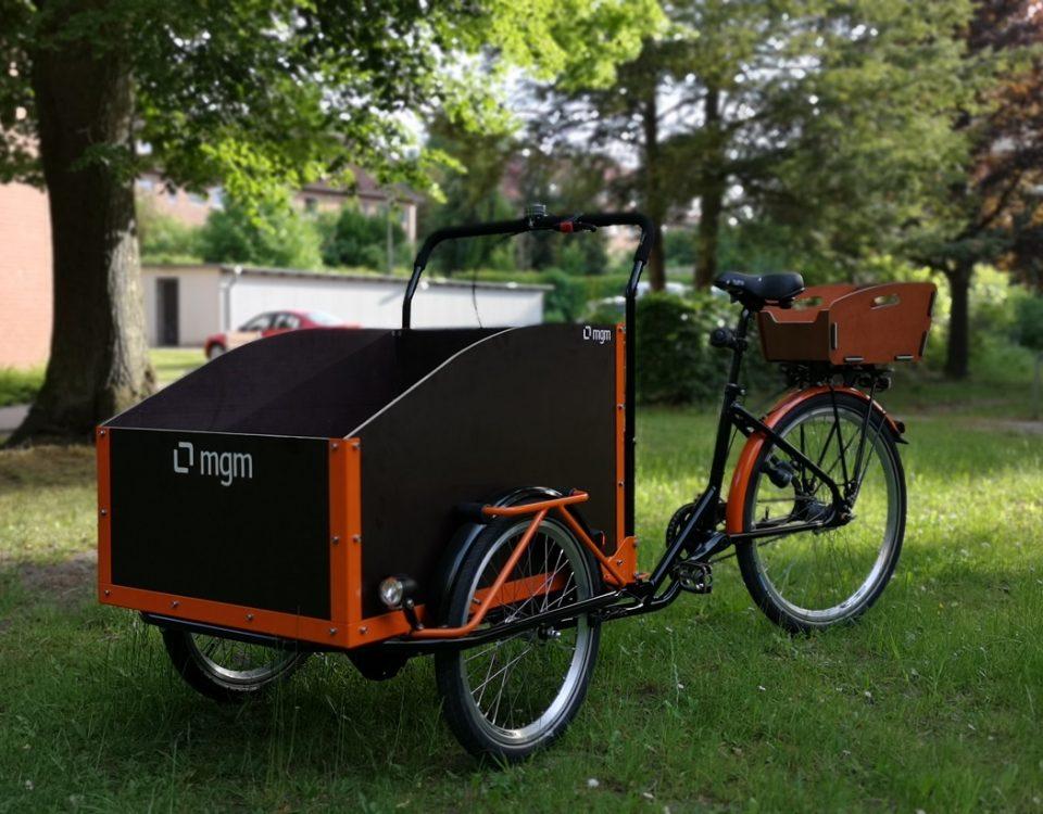 Cargobike mit Holzkiste hinten und Transportbox vorn