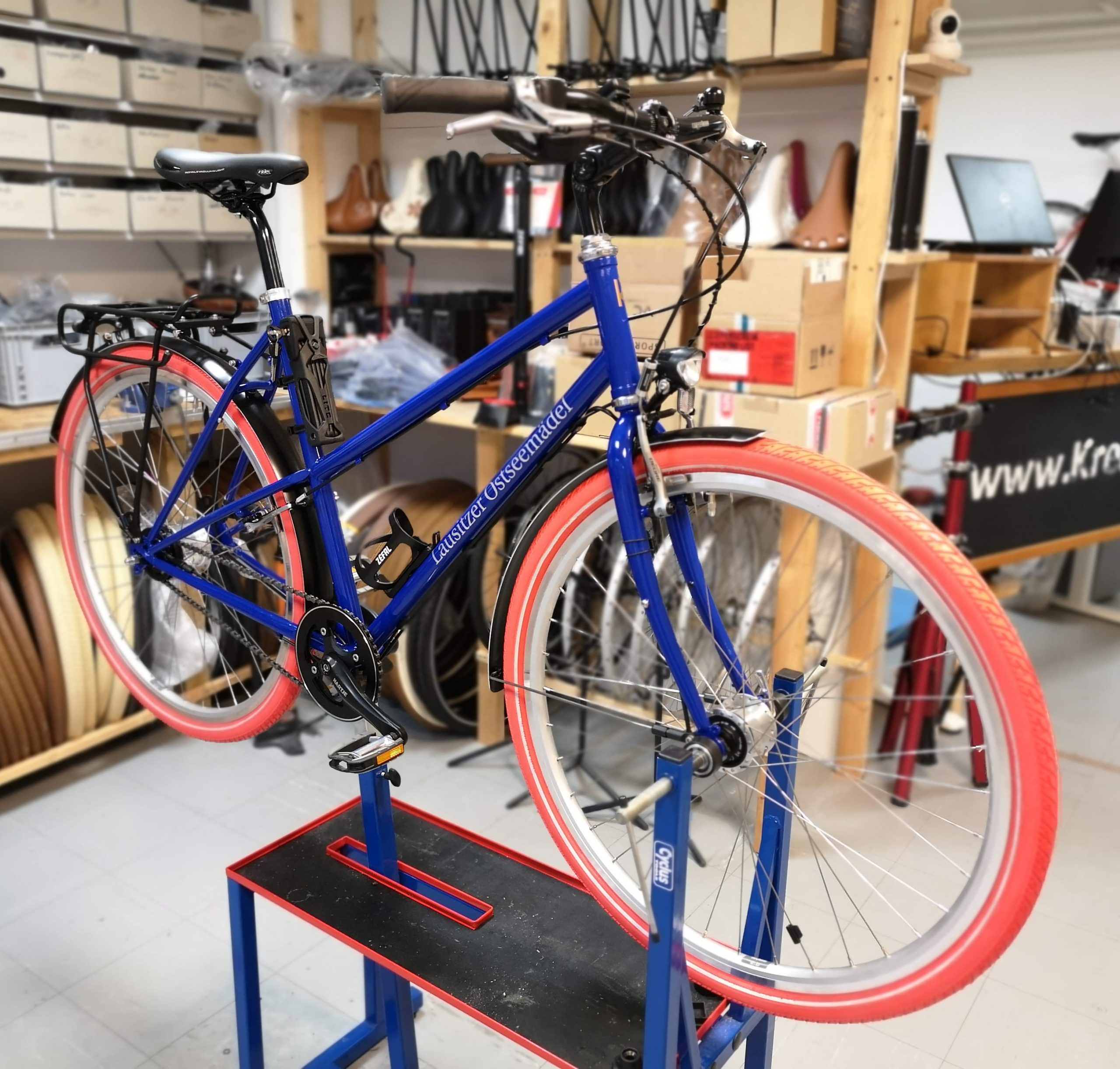 Stahlrahmen Fahrrad in Ultramarienblau. Fahrrad mit roten Reifen und individueller Beschriftung.