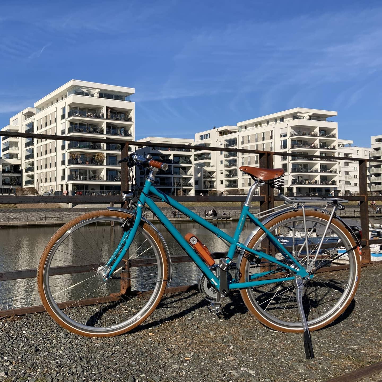 Stahlrahmen Fahrrad in Wasserblau von KreativRad. Mit Brooks B 67 Ledersattel in Braun und braunen Ledergriffen von Brooks. Braunen Reifen von Schwalbe und einer Nabenschaltung von SHIMANO Alfine mit 8-Gängen.