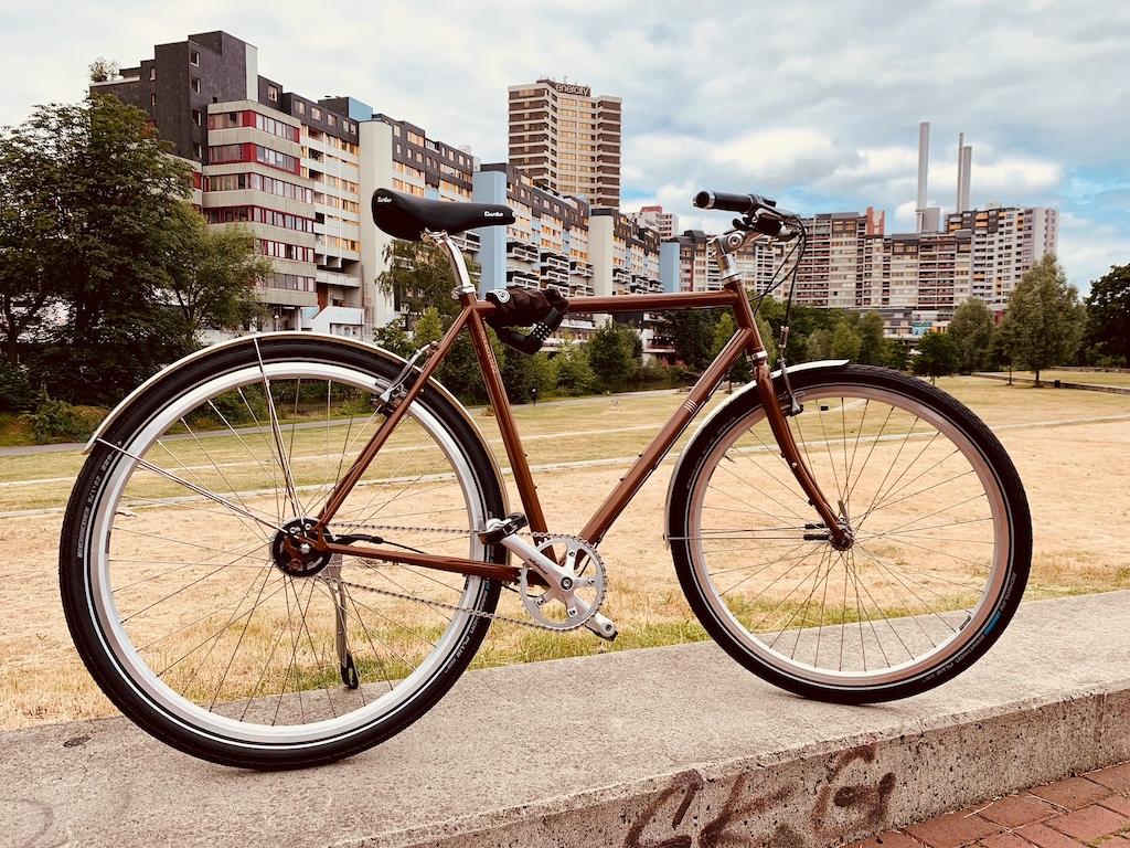 Stahlrahmen Fahrrad in Rehbraun RAL 8007 mit Selle Italia Sattel Turbo 1980 in schwarz, SELLA BEROLINUM Griffen B3 Ergo in schwarz und 11-Gang SHIMANO Alfine. Gesichert wird das Fahrrad mit einem Schloss der Firma ABUS Brodo 6000.
